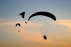 Motorized paragliders. Paramotor gliders silhouettes over sunset sky Stock Photo