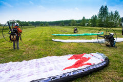 Motorized paragliders are ready to go from a green field Royalty Free Stock Photography