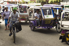Motorized tricycle traffic. Iloilo, Philippines - February 13, 2016. Motorized tricycle Traffic in Iloilo Philippines, and a man with green bandanas riding a Royalty Free Stock Photography