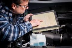 Motormekanikern kontrollerar ett luftfilter för smuts för utbyte arkivbild
