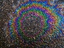 Motorolie op natte weg wordt gemorst - regenboogeffect dat stock afbeeldingen