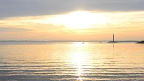 Motorowa łódź rusza się na wodzie przy wschodem słońca z latarnią morską przy świtem zdjęcie wideo