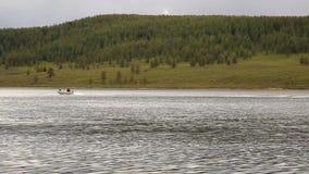 Motorowa łódź unosi się na halnym jeziorze wycieczkuje i łowi w górach, zbiory