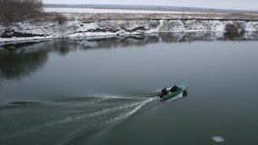 Motorowa łódź unosi się na rzecznej zimie spearfishers zbiory