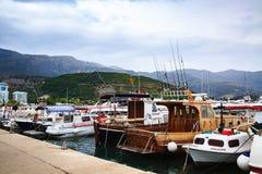 Motorowe łodzie i żaglówki dokowali w schronieniu przeciw górom Łodzie rybackie przy molem w chmurnym dniu obraz stock