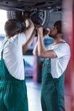 Motorowi mechanicy pracuje w garażu zdjęcia royalty free