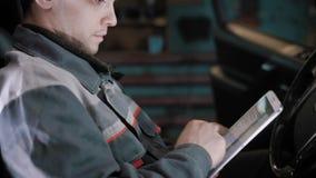 Motorowy mechanik siedzi wśrodku samochodu w garażu, używać pastylkę, podsadzkowi dane samochodu diagnostyk zbiory wideo