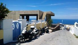 Motorräder in einer schmalen Straße von Oia auf Santorini lizenzfreie stockfotografie