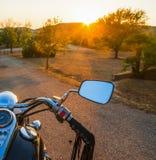 Motorrad auf einer Landstraße bei Sonnenuntergang Lizenzfreie Stockfotografie