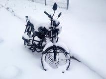 Motorrad bedeckt mit Schnee in der Stadt im Parkplatz Lizenzfreie Stockfotos