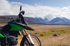 Motorrad enduro Reisender allein unter einem blauen Himmel mit weißen Wolken auf einem Hintergrund des Gebirgstales mit Schneeeis Stockbild