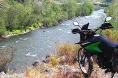 Motorrad enduro Reisender, der auf einem Spitzenhügel über dem Flussstrom auf dem Hintergrund der Felshügel Altai-Berge steht Stockbilder
