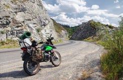 Motorrad enduro Reisender mit den Koffern, die auf Asphaltstraßeweg auf einem montain Durchlauf im Steinfelsen stehen Stockfoto