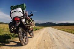 Motorrad enduro Reisender mit den Koffern, die auf Steinschotterwegweg auf einem Bergplateau mit dem grünen Gras stehen Lizenzfreies Stockfoto