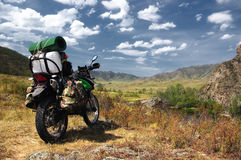 Motorrad enduro Reisender mit Koffern im Gebirgstal auf dem Hintergrund der Felshügel Stockfotografie