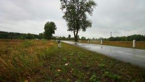 Motorrad-Geschwindigkeiten entlang nasser Straße zwischen Feldern in der Landschaft stock footage