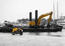 Motorrad mit einem Bagger im Schwarzen und im Gelb Lizenzfreies Stockbild
