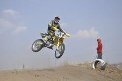 Motorrad-Rennläufer führt einen effizienten Sprung durch Stockbild