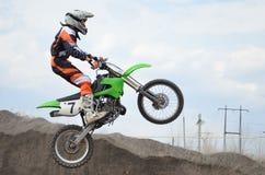 Motorrad-Rennläufer springt über einen hohen Damm von Erde Lizenzfreies Stockbild