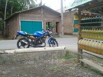 Motorrad am Straßenhaus lizenzfreie stockfotografie