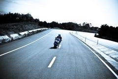 Motorrad, welches die Straße weitergeht Stockfoto