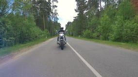 Motorradfahrer ändert Wege und reitet weg an einer Landstraße 4K stock video