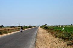 Motorradfahrer auf der Landstraße umgeben durch grüne Bauernhoffelder nahe Mirpurkhas Sindh Pakistan Lizenzfreies Stockbild