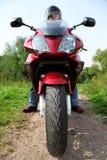 Motorradfahrer, der auf Landstraße, Nahaufnahme steht Lizenzfreies Stockbild