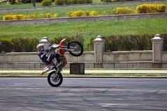 Motorradfahrer, der einen Wheelie tut Stockbild