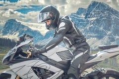 Motorradfahrer in der schneebedeckten Straße, chilenische Berge Stockfotografie