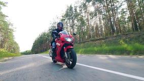 Motorradfahrer, der sein Motorrad läuft Asphaltstraße mit einem Radfahrer, der ein Motorrad fährt stock video footage