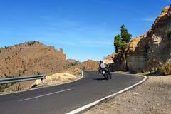 Motorradfahrer, die auf Straße durch Berge an Nationalpark Teide auf Teneriffa-Insel, Spanien fahren Stockfotos