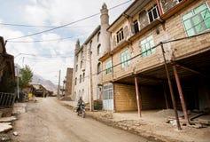 Motorradfahrer geht hinter die Backsteinhäuser des iranischen Dorfs Stockbild