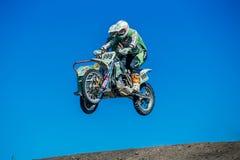 Motorradfahrer mit einem Beiwagensprung von einem Berg auf Hintergrund des blauen Himmels Lizenzfreies Stockfoto