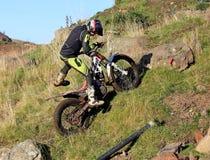 Motorradfahrer mit zwei Versuchen, der oben ein Hügel geht Lizenzfreies Stockbild