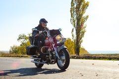 Motorradfahrer Riding Custom Chopper Bike auf Herbstlandstraße Binokel auf der Bootsstrichleiter auf Wasserhintergrund lizenzfreie stockbilder