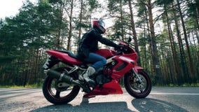 Motorradfahrer sitzt auf einem roten Fahrrad auf einer Straße stock video