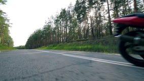Motorradfahrer tut eine Bremsung beim Bewegen Radfahrerreiten hinunter Landstraße stock video