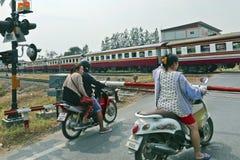Motorradfahrer warten auf einen Zug, um an einem Bahnniveauübergang zu überschreiten stockfotografie