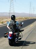 Motorradfahrerfahrten one-handed durch die Wüste stockbilder