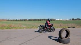 Motorradfahrertanzen nahe einem Motorrad stock video footage