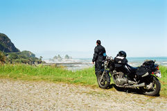 Motorradmitfahrer-Betrachtungsozean Stockfotos