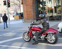 Motorradreiter, der am roten Licht wartet Stockfotografie