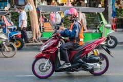 Motorradtaxifahrer-Gebrauchsmobiltelefon auf Fahrrad in Bangkok Stockfoto