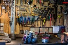 Motorradteile und -werkzeuge auf dem Desktop in der Garage Stockbilder