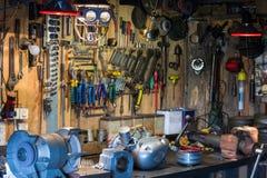 Motorradteile und -werkzeuge auf dem Desktop in der Garage Lizenzfreies Stockbild
