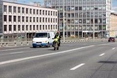 Motorrijder en minibus op de weg tegen de achtergrond van moderne gebouwen stock afbeeldingen