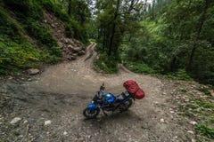 Motorrijder op een bergachtige weg, koud donker weer Extreme sport, Sainj-Vallei, Himachal Pradesh, India stock afbeeldingen
