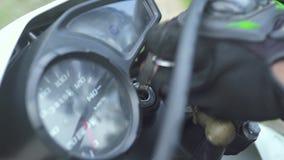Motorrijderhand die sleutel voor beginnende motorfietsmotor opnemen Sluit omhoog de beginnende motorfiets van de motofietser voor stock videobeelden