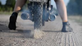 Motorrijderritten weg op een motorfiets langs een zandige weg stock videobeelden
